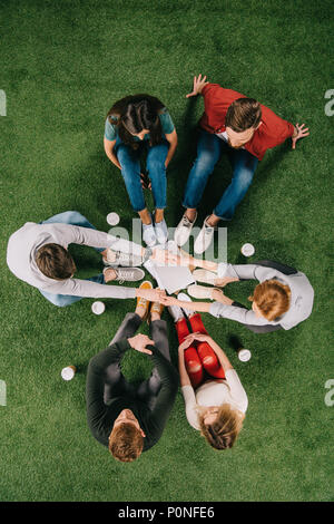 overhead view of business partners holding hands and sitting with another colleagues on grass - Stock Photo