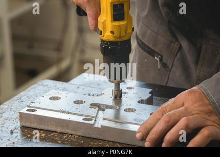 Male working hands drilling industrial metal object - Stock Photo