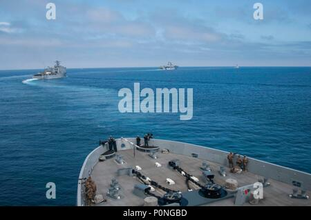 180604-N-YJ378-0109 PACIFIC OCEAN (June 4, 2018) San Antonio-class amphibious transport dock USS Anchorage (LPD 23), maneuvers into position for a strait transit exercise behind Whidbey Island-class amphibious dock landing USS Rushmore (LSD 47), left, Wasp-class amphibious assault ship USS Essex (LHD 2), center, and Arleigh Burke-class guided-missile destroyer USS Decatur (DDG 73), right, during a composite training unit exercise (COMPTUEX). COMPTUEX is the final pre-deployment exercise which certifies the combined Essex Amphibious Ready Group and the 13th Marine Expeditionary Unit's abilities - Stock Photo
