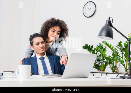African american woman showing something on laptop screen to her male colleague - Stock Photo