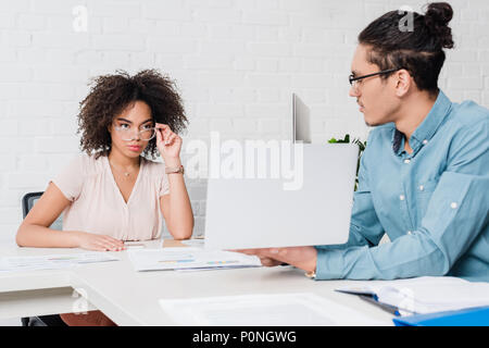 Businessman showing something on laptop to african american businesswoman in office - Stock Photo