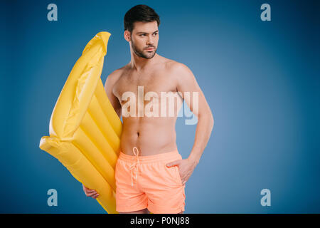 handsome young man in shorts holding swimming mattress and looking away on blue - Stock Photo