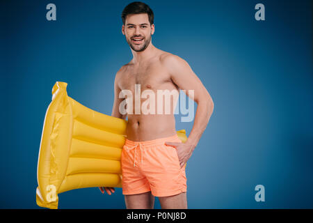 handsome young man in shorts holding swimming mattress and smiling at camera on blue - Stock Photo