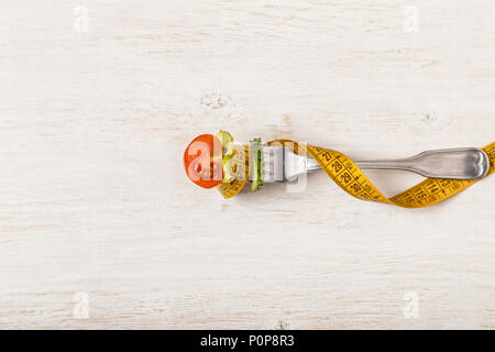 Fresh salad on a fork, tape measure, top view. The concept of diet, healthy food - Stock Photo