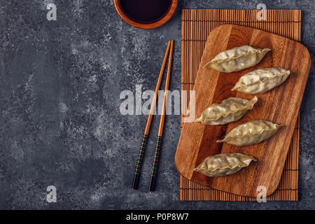 Fresh dumplings on a dark stone background. Asian cuisine, top view, copy space. - Stock Photo