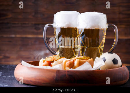 Photo of two mugs of beer and hot dogs on wooden tray with football - Stock Photo