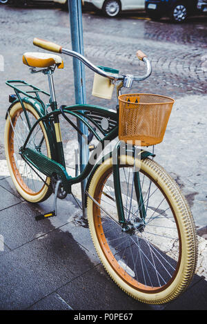 vintage bicycle with basket parked on street of Rome, Italy - Stock Photo