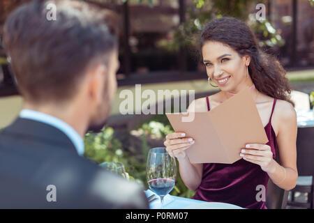 Couple having romantic date in restaurant, woman choosing meal in menu - Stock Photo