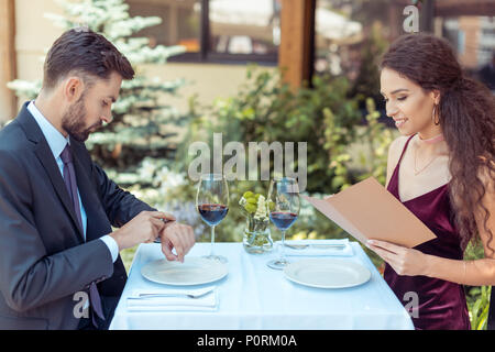 Couple having romantic date in restaurant, woman choosing meal in menu, man looking at watches - Stock Photo