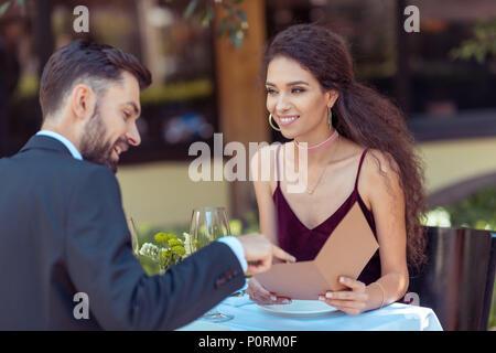 Couple having romantic date in restaurant, choosing meal in menu - Stock Photo