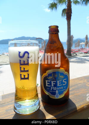 A bottle of Efes Pilsen lager beer taken in a bar on the beach promenade, Marmaris, Mugla province, Turkey - Stock Photo