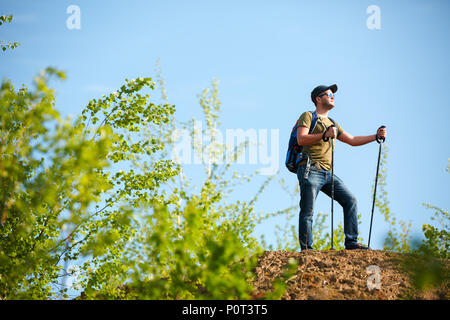 Photo of man with backpack and walking sticks on hill - Stock Photo