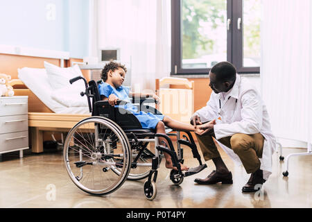 side view of african american doctor examining foot of disabled patient in wheelchair in clinic - Stock Photo