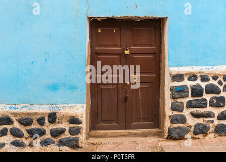 Colourful facade with wooden door in the city center of Potosi (Unesco World Heritage Site), famous for its colonial architecture, Bolivia. - Stock Photo