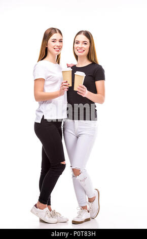cheerful twins with coffee to go in hands looking at camera isolated on white - Stock Photo