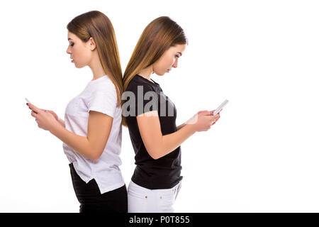 side view of twins standing back to back and using smartphones isolated on white - Stock Photo