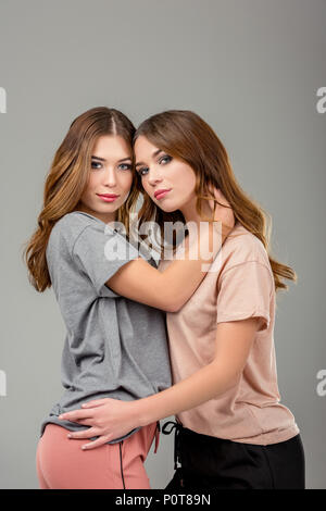 portrait of beautiful twin sisters hugging each other and looking at camera isolated on grey - Stock Photo