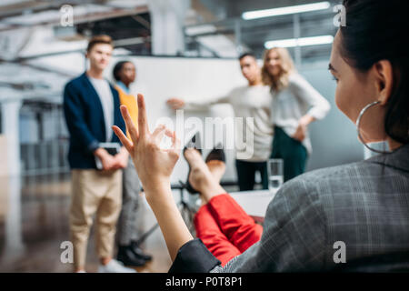 managers making presentation for lady boss while she showing okay sign - Stock Photo