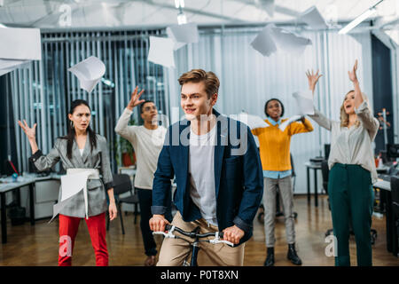 young businessman riding bike at office while partners throwing up papers on background - Stock Photo