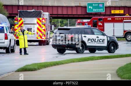 May 18 2018 Stevensville MI USA; A police man in rain gear directs traffic at the scene of a bad accident, with fire trucks waiting behind him - Stock Photo