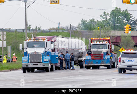 May 18 2018 Stevensville MI USA;people stand near a tow truck and a very smashed truck at the scene of an accident - Stock Photo