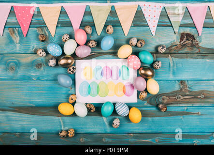top view of colorful happy easter greeting card with colorful eggs around on blue wooden planks - Stock Photo