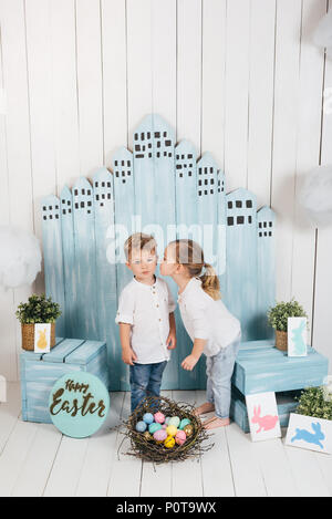 adorable little kids kissing in easter decorations - Stock Photo