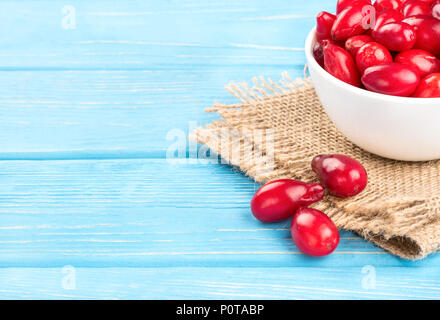 Fresh dogwood berries in the bowl on the table and sacking, closeup - Stock Photo