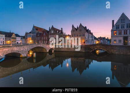 Dusk lights on the historic buildings of the city centre reflected in the typical canals Bruges West Flanders - Stock Photo