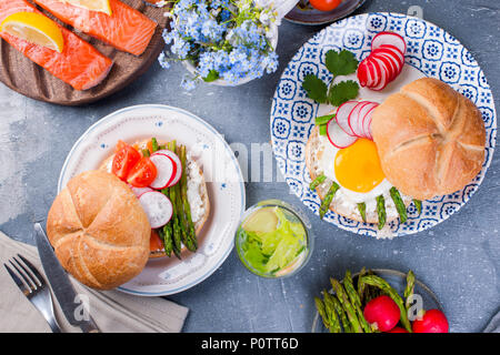 Bread with cheese, egg and asparagus, another bread with salmon and. asparagus. Healthy food. Tasty breakfast. Gray background. - Stock Photo