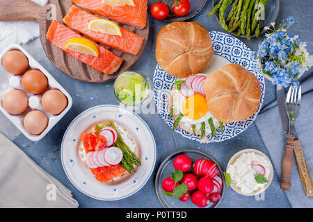 Bread with cheese, egg and asparagus, another bread with salmon and. asparagus. Healthy food. Tasty breakfast. Gray background - Stock Photo