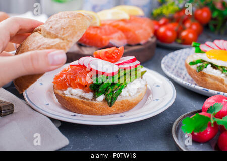 Bread with cheese, radish, salmon and asparagus, in a woman's hand. Different Healthy Eating. Delicious breakfast for the family. Food in the Netherlands. - Stock Photo