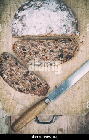 Organic fruit sourdough loaf with bread knife on a wooden board. UK. Vintage filter applied - Stock Photo
