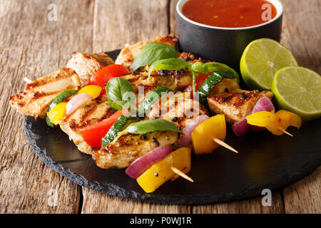 Served grilled chicken kebab skewers with vegetables with sauce, herbs and lime closeup on a slate plate on a table. horizontal - Stock Photo