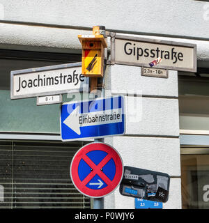 Bird nesting box on a pole with street signs and traffic signs in an urban street in Berlin - Stock Photo