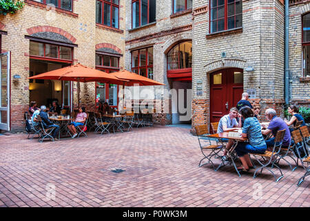 Berlin, Mitte Sophie-Gips-Höfe Barcomis Deli, coffee shop & diner in inner courtyard of old  historic brick factory building.People at outdoor tables - Stock Photo