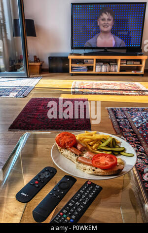 Informal supper, TV dinner, Designer Hotdog on olive bread with chips,mustard,tomatoes and pickled cucumbers - Stock Photo