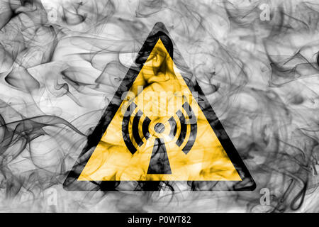 Non ionising electromagnetic radiation hazard warning smoke sign. Triangular warning hazard sign, smoke background. - Stock Photo