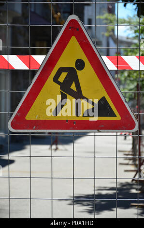 The warning sign 'under construction' is attached to a metal mesh fence with a red and white striped signal tape - Stock Photo