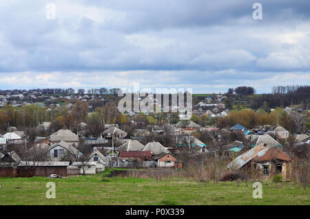 A rural landscape with many private houses and green trees. Suburban panorama on a cloudy afternoon. A place far from the city - Stock Photo