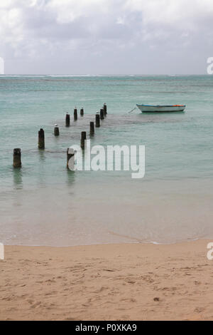 Sandy coast, destroyed pier and boat. Anse de Sent-An, Pointe-a-Pitre, Guadeloupe - Stock Photo