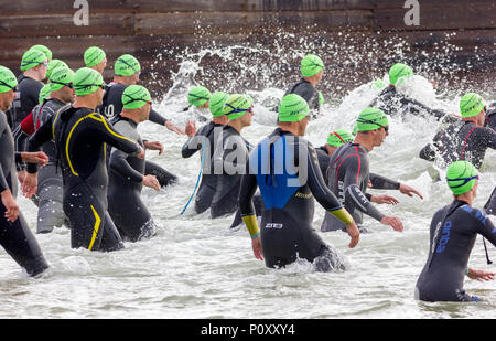 Eastbourne, East Sussex, UK. 10th June 2018. Hundreds take part in the annual Eastbourne Triathlon. The race consisting of a swim, cycle and run starts before 8am with a 600m swim from the Eastbourne seafront. The two groups taking part consist of the elite athletes followed shortly afterwards into the water by the amateur and fun competitors. This early Sunday morning event attracts crowds of spectators from the local area and nearby hotels to cheer on those taking part. Credit: Alan Fraser/Alamy Live News - Stock Photo