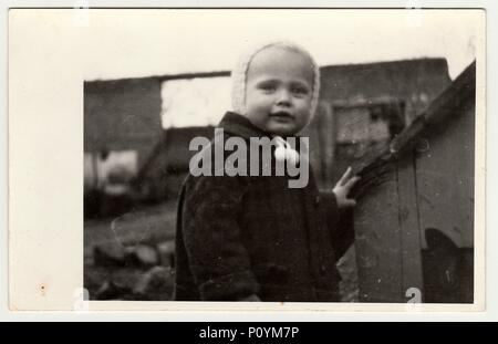 THE CZECHOSLOVAK REPUBLIC, CIRCA 1942: Vintage photo shows a small girl and kannel (doghouse), circa 1942. - Stock Photo