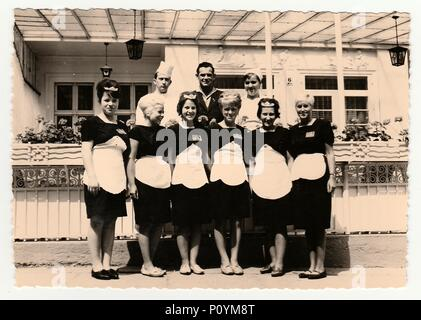 GERMANY, CIRCA 1960s: Vintage photo shows hotel staff in front of hotel, circa 1960s. - Stock Photo