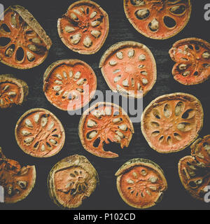 Dried herbs and dried bael fruit, Top view of bael dry on the wooden floor, Slices of bael fruit for make bael juice on the dark table. - Stock Photo