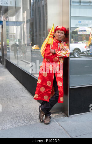 A Vietnamese immigrant in ethnic clothing & holding a South Vietnamese flag  at the Vietnamese American Cultural Parade. - Stock Photo