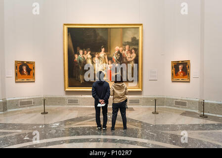 Goya painting Prado, a young couple visiting the Prado Museum in Madrid pause to look at The Family of Carlos IV by Francisco Goya, Spain. - Stock Photo