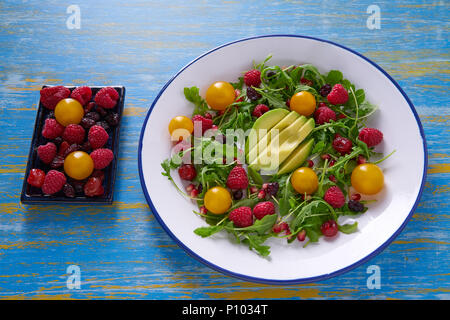 Avocado and berries salad with arugula and yellow cherry tomatoes - Stock Photo