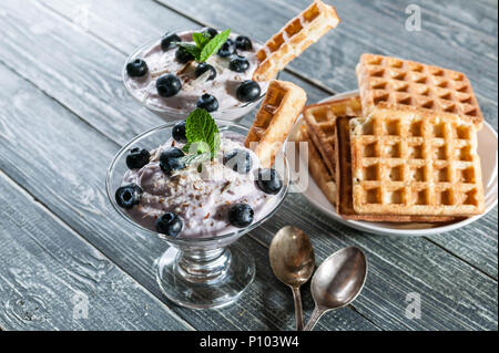 Curd dessert with blueberries in a glass cup and homemade Viennese waffles on a wooden background - Stock Photo