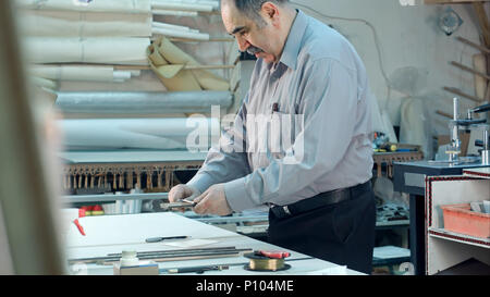 Senior male business owner working in workshop of his frame studio - Stock Photo